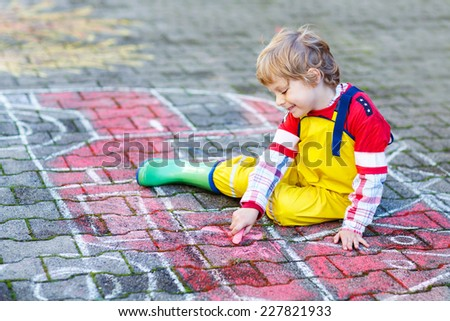 Creative leisure for kids: adorable kid boy clothing as firefighter having fun with fire truck picture drawing with chalk, outdoors. Dreaming of future profession. - stock photo