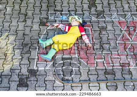 Creative leisure for kids: adorable toddler child  having fun with fire truck picture drawing with chalk, outdoors. Dreaming of future profession. - stock photo