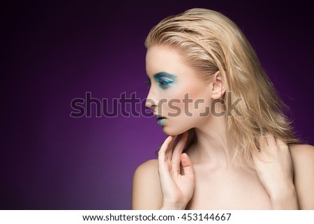 Creative look. Beautiful blonde fashion model with metallic lips and blue eye makeup looking at the copyspace touching her face on violet background - stock photo