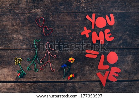 Creative love message. Couple holding hands made from paper clips and and thumbtacks on vintage background.  - stock photo