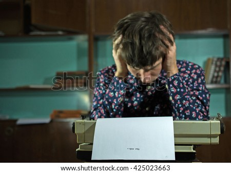 Creative man hold had in hands before typewriter with clear white sheet. Creative crisis, stress, creative stupor concept. - stock photo