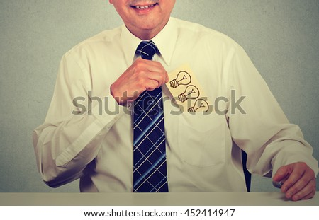 Creative middle aged businessman with a great idea withdrawing card with a hand drawn light bulb from his shirt pocket, retro filter effect applied. Businessman with idea sitting at his office table - stock photo