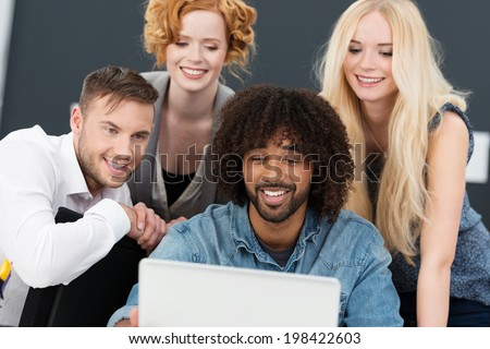 Creative multiethnic young group of business partners working together on a laptop computer grouped around a smiling African American man - stock photo