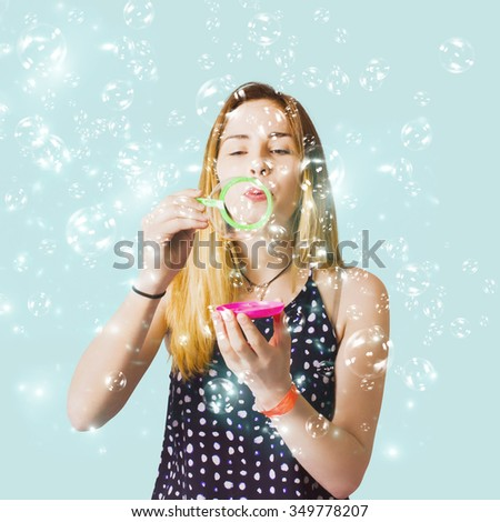 Creative party portrait on a playful woman blowing party bubbles in a special occasion birthday celebration on aqua background. Thank you guest - stock photo