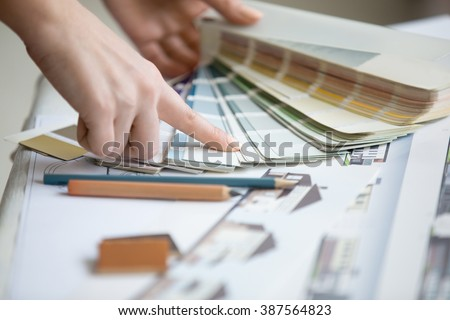 Creative people workplace. Close-up view of hands of young designer woman working with color palette at office desk. Attractive model choosing color samples for design project. Interior shot - stock photo