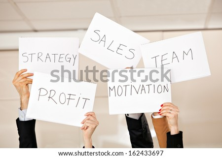 creative photo: five hands holding card boards in the air: strategy, motivation, profit, team, sales - stock photo