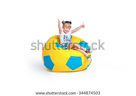Creative photo of cute little girl isolated on white background. Girl smiling, showing thumbs up and sitting on big frameless football chair - stock photo