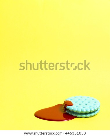 Creative photo of mint cracker covered with red paint on yellow background. - stock photo