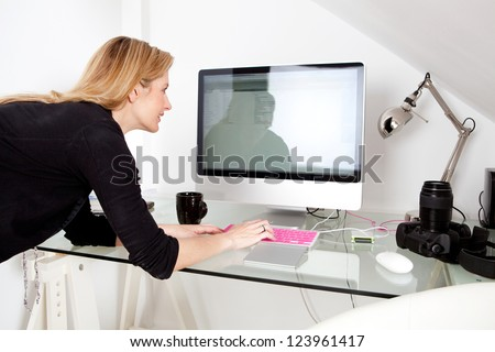 Creative photographer woman professional using a desktop computer and typing on a keyboard, busy at work with photographic equipment. - stock photo