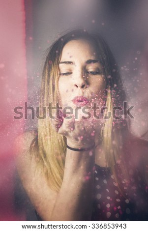 Creative pink abstract portrait on the face of a beautiful woman blowing a burst of magic glitter at valentine's day party celebration. Valentine girl making wish kiss - stock photo
