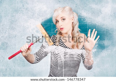 Creative pinup portrait of an attractive young housewife cleaning glass shower door with white soap suds and squeegee. Clean copyspace  - stock photo
