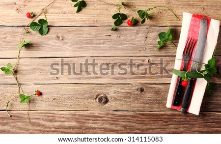 Creative place setting with fresh plants and berries forming a trailing border around copyspace on a wooden table with utensils and a red and white napkin - stock photo
