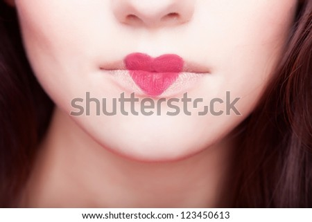 Creative portrait of a beautiful young girl with a heart painted on his lips - stock photo
