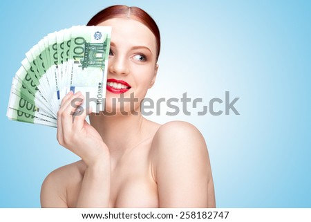 Creative portrait of a nude girl with beautiful face and body holding hand fan made of 100-euro currency banknotes on blue background. - stock photo