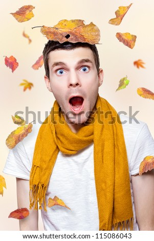 Creative Portrait Of A Shocked Man With Mouth Wide Open Playing In Falling Autumn Leaves - stock photo