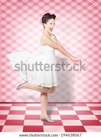 Creative portrait of an attractive pinup woman with expression of surprise running at speed in vintage kitchen with motioning white dress. Retro rush - stock photo