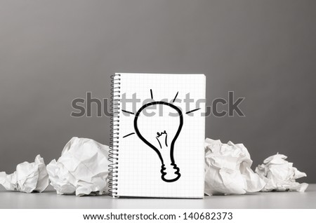 creative process. crumpled wads and notebook with bulb picture - stock photo