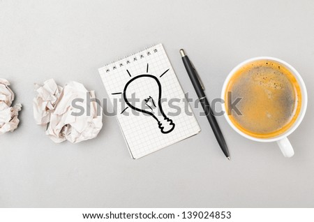creative process. crumpled wads, notebook with bulb picture and cup - stock photo