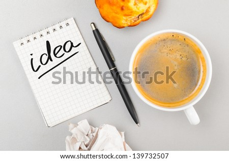 creative process. crumpled wads, notebook with idea word and cup - stock photo