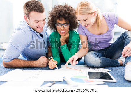Creative professionals working on floor  - stock photo