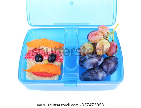 Creative sandwich and fruits in plastic lunchbox isolated on white background - stock photo