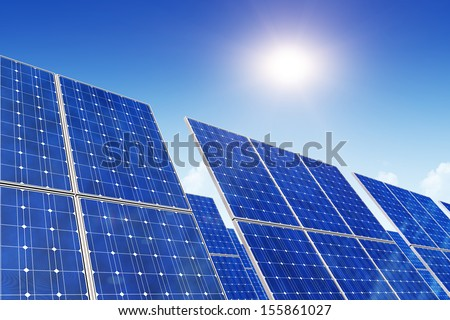 Creative solar power generation technology, alternative energy and environment protection ecology business concept: group of solar battery panels against blue sky with sun light - stock photo