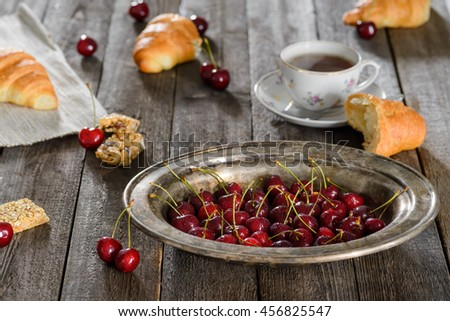 Creative still life made of food and the cup of tea. Scattered croissants, cherries and broken brittles on the vintage wooden table. - stock photo