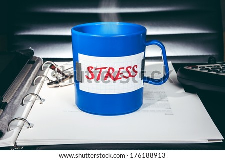"Creative stress concept. A blue mug with a message ""Stress"" standing on a desk with business accessories. - stock photo"