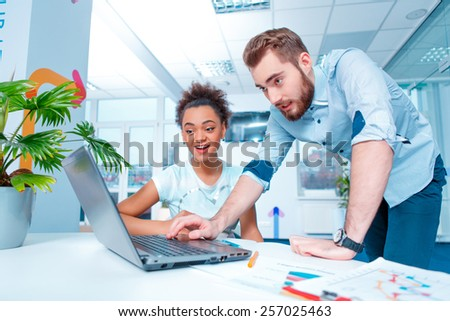 Creative team at work. Young African woman and Caucasian man in smart casual looking at laptop together while sitting in creative space  - stock photo