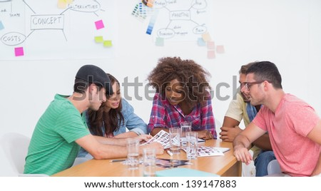 Creative team brainstorming over contact sheets in office with whiteboard - stock photo