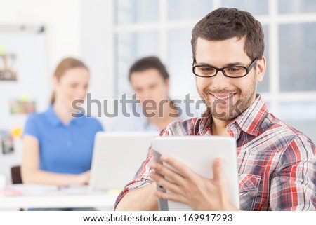 Creative team. Cheerful young man in glasses using digital tablet and smiling while his colleagues working on the background - stock photo