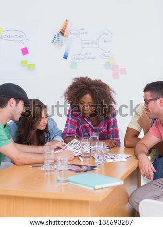 Creative team talking over contact sheets in meeting in office with whiteboard - stock photo