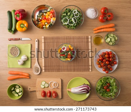 Creative vegetarian cooking at home concept with fresh healthy vegetables chopped, salads and kitchen wooden utensils, top view with copy space - stock photo