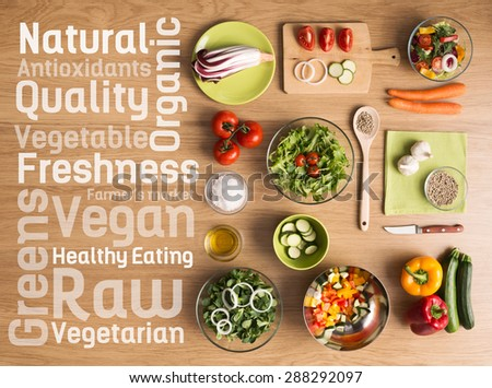 Creative vegetarian cooking at home with fresh healthy vegetables chopped, salads and kitchen wooden utensils, healthy eating text concepts on the left - stock photo