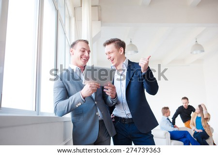 Creative work and technology. Two smiling handsome men using tablet computer while discussing something with their colleagues in the background. - stock photo
