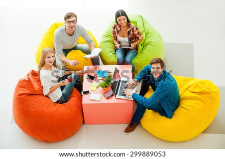Creative work space. Top view of four cheerful young people working together and looking up while sitting at the colorful bean bags - stock photo