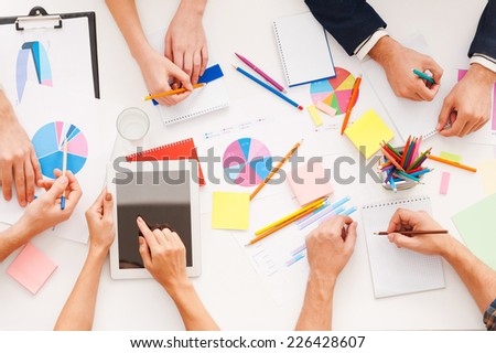 Creative work. Top view of business people working together while sitting at the table - stock photo