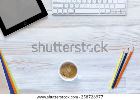 Creative working desk with coffee mug in the center.  Top view on working place with cup of coffee, tablet PC, computer keyboard, and color matching booklets and pencils. - stock photo