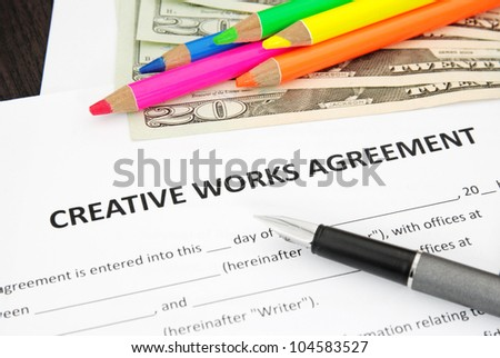 Creative Works Agreement with money dollar and crayons - stock photo
