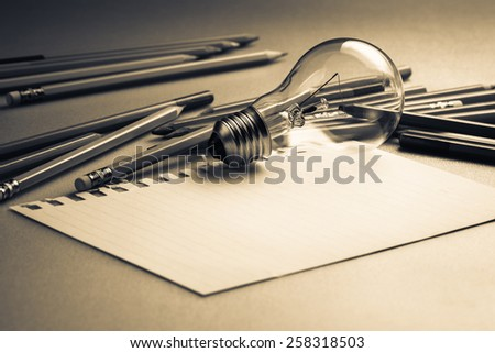 Creative writing, light bulb and many pencils on the table - stock photo