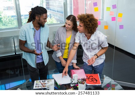 Creative young business people working at office desk - stock photo