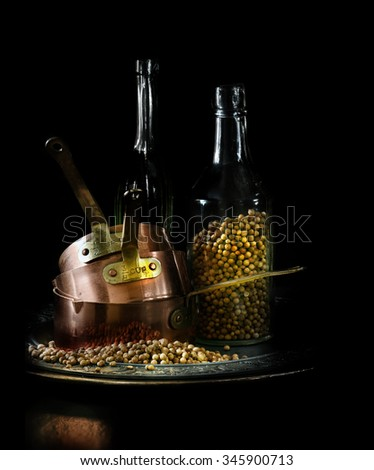 Creatively lit Indian copper measuring pans with fresh coriander seeds, also called cilantro seeds, against a black background. Concept image for Indian cooking. Copy space. - stock photo