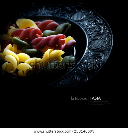 Creatively lit Italian tricolore pasta on a pewter plate against black. Concept image for vegetarian food. Copy space. - stock photo