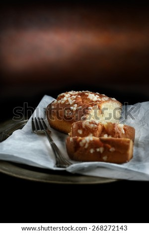Creatively lit with selective focus homemade lemon drizzle sponge cake against a dark rustic background. The perfect image for your dessert menu cover design. Copy space. - stock photo