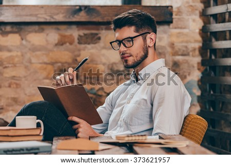 Creativity at work. Side view of handsome young man holding note pad and looking at it while sitting at his working place - stock photo