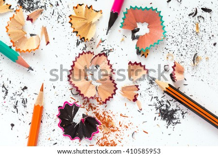 Creativity Concept Image of color Pencils and shaped wood Chips and Shavings of sharpening a pencil on white Table - stock photo