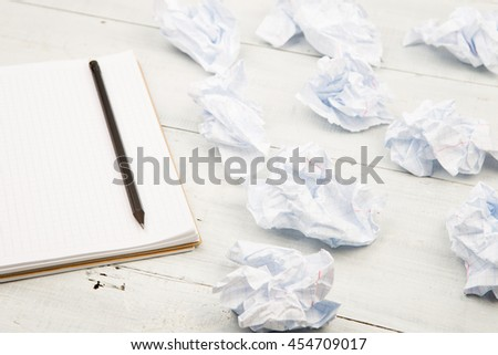 Creativity concept - notepad, pencil and crumpled paper on white wooden table - stock photo