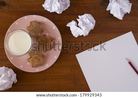 Creativity concept. Pencil on a white paper with crumpled paper ball, a pink plate with star cookies and a glass of milk. All on a wooden table. - stock photo