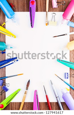 Creativity ready. White sheet of paper spread out around the brushes, scissors, paints and small details. - stock photo