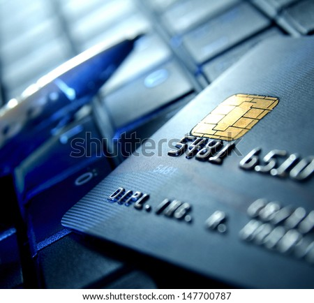 Credit card and ball pen on a laptop - stock photo